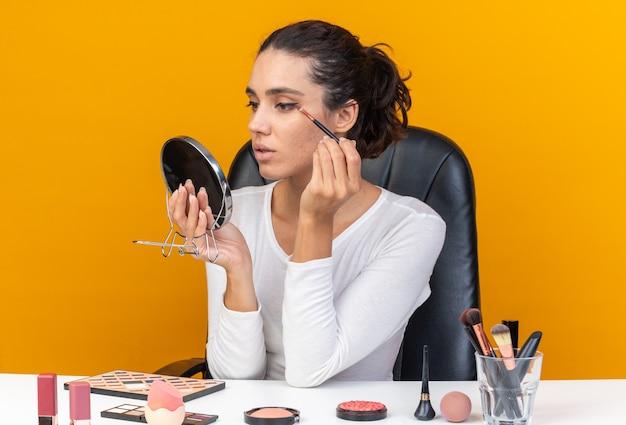 Donna abbastanza caucasica sicura seduta al tavolo con strumenti per il trucco che tiene e guarda lo specchio applicando l'ombretto isolato sulla parete arancione con spazio di copia
