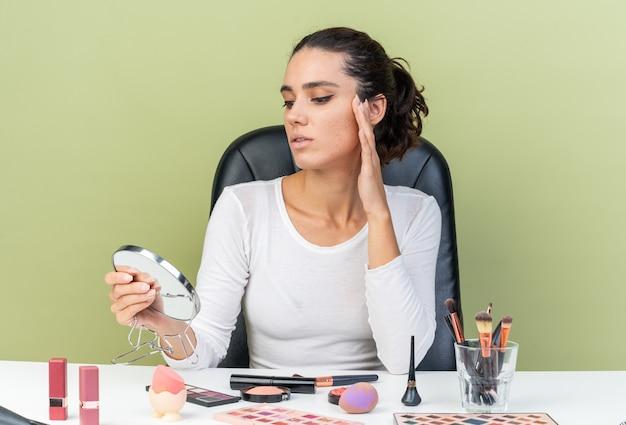 Donna abbastanza caucasica fiduciosa seduta al tavolo con strumenti per il trucco che tiene e guarda lo specchio isolato su parete verde oliva con spazio di copia