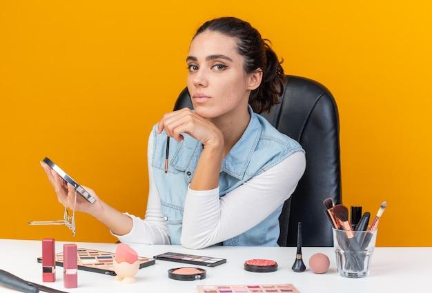 Donna abbastanza caucasica sicura che si siede al tavolo con strumenti per il trucco che tengono pennello per il trucco e specchio isolato sulla parete arancione con spazio di copia