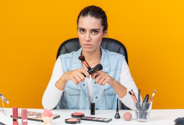 Donna abbastanza caucasica sicura che si siede alla tavola con gli strumenti di trucco che tengono i pennelli di trucco