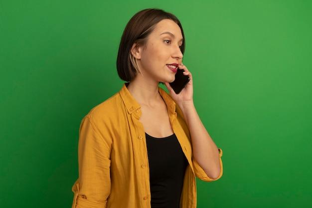 自信を持ってかなり白人女性が横向きに立って緑の電話で話している