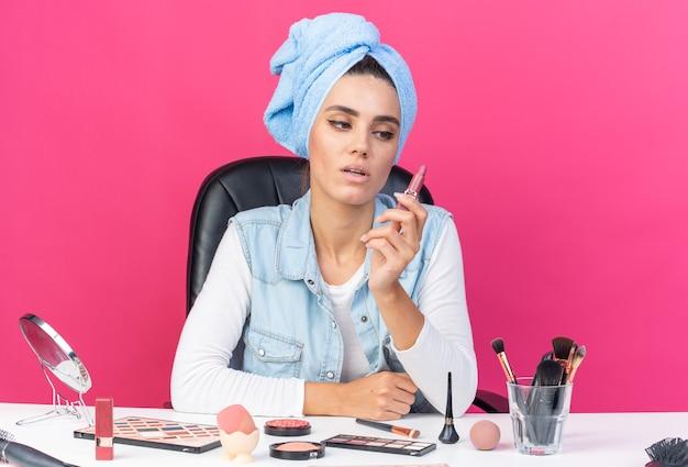 口紅を持って見ている化粧ツールでテーブルに座ってタオルで包まれた髪を持つ自信を持ってかなり白人女性