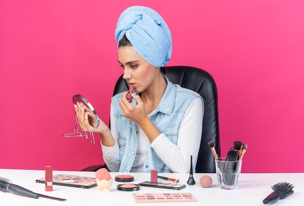 Уверенная в себе симпатичная кавказская женщина с обернутыми волосами в полотенце сидит за столом с инструментами для макияжа и смотрит в зеркало, применяя помаду