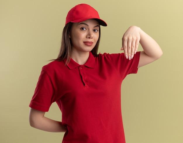 제복을 입은 자신감이 예쁜 배달 여자가 올리브 그린에 손을 거꾸로 보유하고 있습니다.