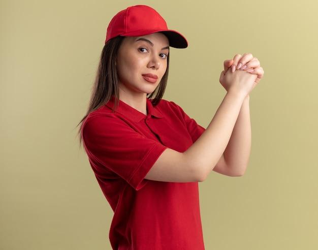 制服を着た自信のあるかわいい分娩女性がオリーブグリーンで手をつなぐ