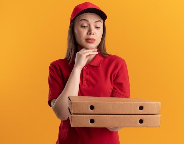 제복을 입은 자신감 있는 예쁜 배달 여성은 턱을 잡고 복사 공간이 있는 주황색 벽에 격리된 피자 상자를 보고 있습니다.