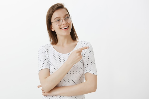 Confident pretty female developer, student pointing right, making choice