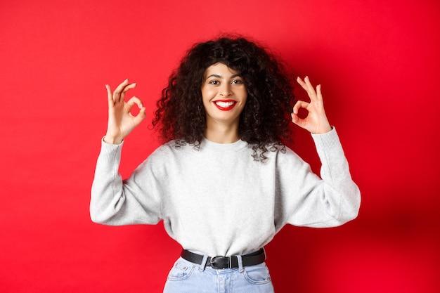 巻き毛の髪型で自信を持ってかわいい女の子、大丈夫なジェスチャーと笑顔を示し、あなたを承認して同意し、優れた選択を賞賛し、赤い背景に満足して立っています