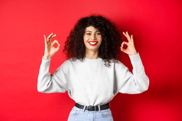 Confident pretty girl with curly hairstyle, showing okay gestures and smiling, approve and agree with you, praising excellent choice, standing satisfied on red background.