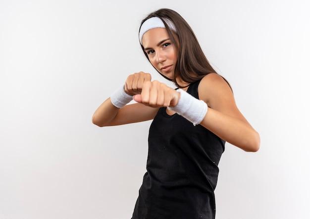 Уверенная, симпатичная спортивная девушка с повязкой на голову и браслетом делает боксерский жест, изолированные на белой стене с копией пространства