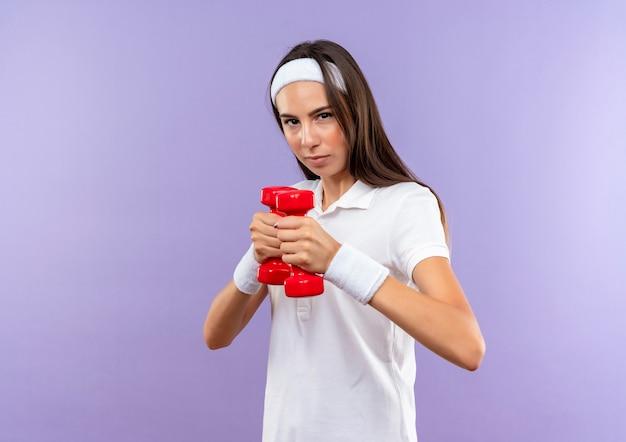 Уверенная, симпатичная спортивная девушка с повязкой на голову и браслетом с гантелями, изолированными на фиолетовой стене с копией пространства