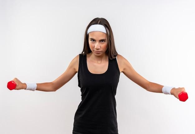 흰 벽에 고립 된 두 팔을 벌려 아령을 들고 머리띠와 팔찌를 착용하는 자신감이 꽤 스포티 한 소녀
