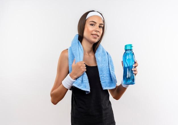 Fiduciosa ragazza abbastanza sportiva che indossa fascia e cinturino che tiene una bottiglia d'acqua e un asciugamano intorno al collo isolato su un muro bianco