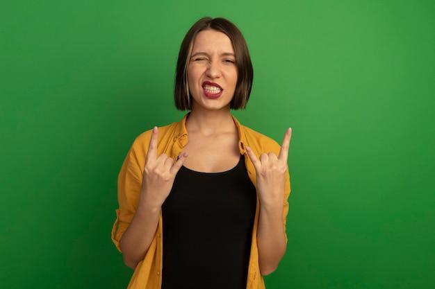 자신감이 예쁜 여자는 녹색 벽에 고립 된 두 손으로 눈과 제스처 뿔 손 기호를 깜박입니다