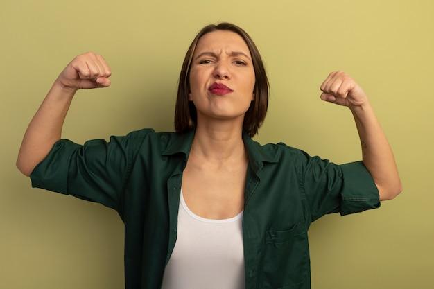 自信を持ってきれいな女性はオリーブグリーンの壁に分離された上腕二頭筋を緊張させる