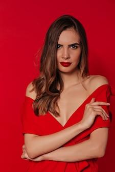 Уверенная красивая женщина с волнистыми волосами в красном платье с красными губами над красной стеной