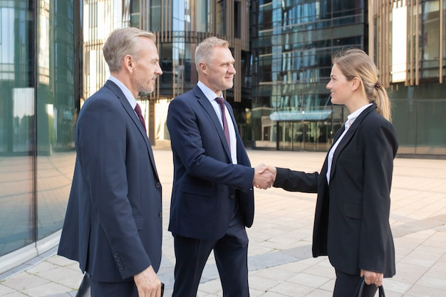 Confident pretty young businesswoman greeting colleagues and smiling. professional successful content managers standing outdoors, making agreement and handshaking. teamwork and partnership concept