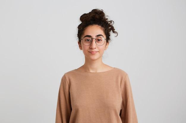 暗い巻き毛の束を持つ自信を持ってかなり若い女性の学生はベージュのプルオーバーを身に着けており、眼鏡は平和を感じ、白い壁に隔離された正面を見る真剣で落ち着いた