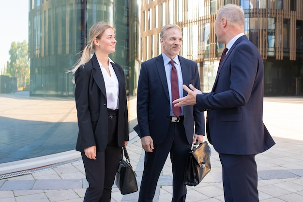 Уверенно профессиональные взрослые бизнесмены, встречающиеся на открытом воздухе. контент деловой мужчина и женщина в костюме, слушая босса и улыбаясь. концепция совместной работы, переговоров и партнерства