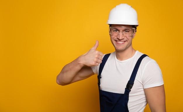 自信のあるプロ。作業服、ヘルメット、透明な眼鏡をかけた魅力的な男性のクローズアップの肖像画。カメラを見て親指を立てています。