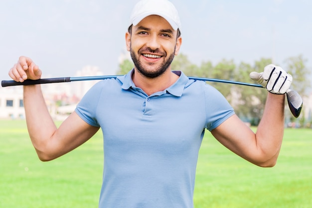 Уверенный в себе профессиональный гольфист. улыбающийся молодой человек с клюшкой для гольфа на плечах, стоя на поле для гольфа