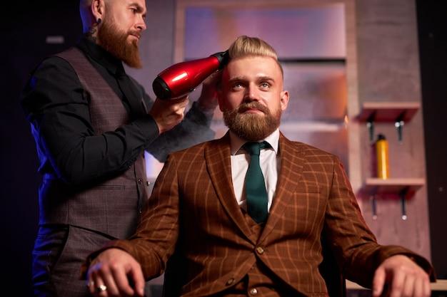 Уверенный профессиональный мужской парикмахер с феном сушит волосы молодого кавказского красавца