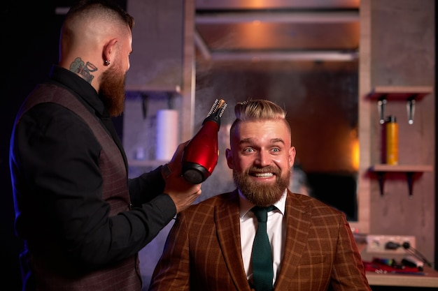 Confident professional male barber with a hair dryer drying a young caucasian handsome man's hair