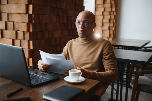 Уверенно преуспевающий молодой топ-менеджер афроамериканского происхождения в строгой рубашке, пьет кофе и делает документы, работает на обычном ноутбуке и пользуется бесплатным беспроводным доступом в интернет в ресторане
