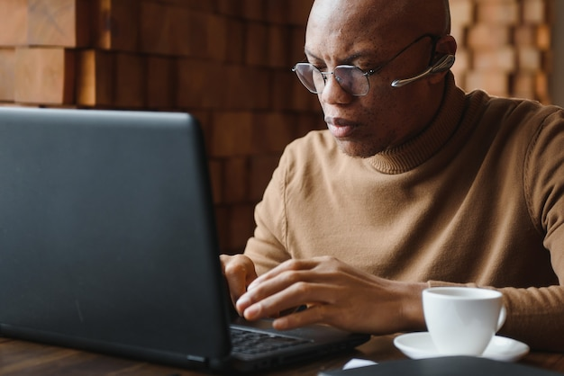 Confident prosperous african-american young top-manager wearing formal shirt having coffee and doing paperwork, working on generic laptop, using free wireless internet connection at restaurant