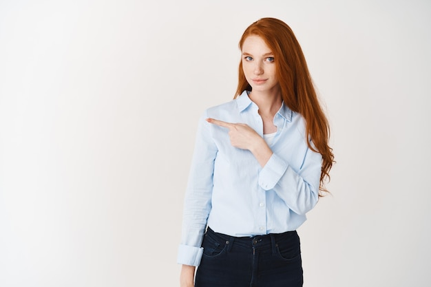 Confident redhead businesswoman pointing finger left, showing company logo on white wall, wearing blue shirt