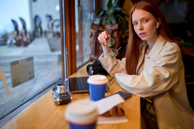 Confident redhead female photographer with modern laptop sitting at cafeteria table and thinking about distance job, contemplative woman with netbook device pondering on idea for web design