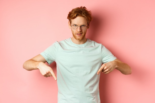 Confident redhead man in glasses pointing fingers down, staring daring with smug face at camera, showing advertisement, standing over pink background.