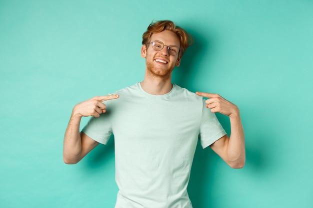 안경과 티셔츠를 입은 자신감 있는 빨간 머리 남자, 늠름한 얼굴로 웃고 자신을 가리키며 청록색 배경 위에 서 있는 동안 자랑합니다.