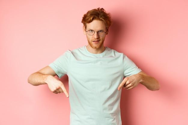 ピンクの背景の上に立って、広告を表示し、カメラで独善的な顔で大胆に見つめ、指を下に向けて眼鏡をかけた自信のある赤毛の男。