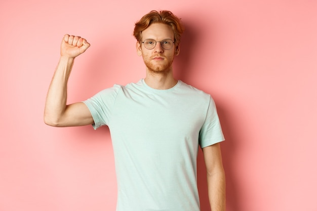 Confident redhead man standing united with black lives matter movemet, showing raised fist and looking serious at camera, protesting and being an activist, standing over pink background.