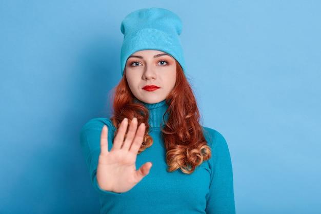자신감 빨강 머리 여자는 앞쪽으로 손바닥을 유지