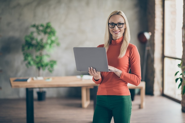 Confident rich wealthy big company owner charming woman stand hold computer type email with partners wear red turtleneck in office loft