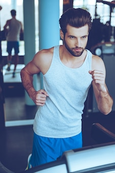 Confident runner. high angle view of young man in sportswear running on treadmill at gym