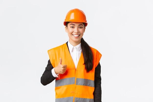安全ヘルメット、反射ジャケット、承認、サポートなどの従業員の仕事のような親指を示し、白い背景に立って自信を持って満足しているアジアの女性建設マネージャー