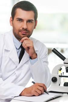 자신감 있는 과학자. 흰색 제복을 입은 잘생긴 젊은 과학자는 턱에 손을 대고 작업장에 앉아 메모장에 글을 씁니다.