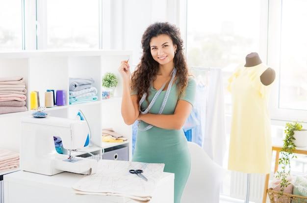 縫製設備を備えたワーク ショップで自信を持って女性
