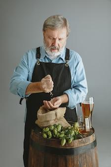 Fiducioso uomo anziano birraio con birra artigianale in vetro sulla botte di legno sul muro grigio. il proprietario della fabbrica ha presentato i suoi prodotti, testandone la qualità.