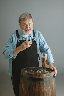 Confident senior man brewer with self crafted beer in glass on wooden barrel on grey wall