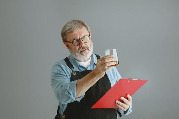 Fiducioso uomo anziano birraio con auto artigianale birra in vetro sulla botte di legno sul muro grigio