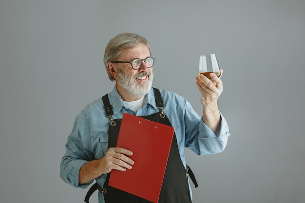 Confident senior man brewer with self crafted beer in glass on wooden barrel on grey