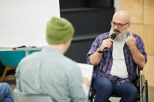 Уверенный старший мужчина в инвалидной коляске, проведение презентации для студентов