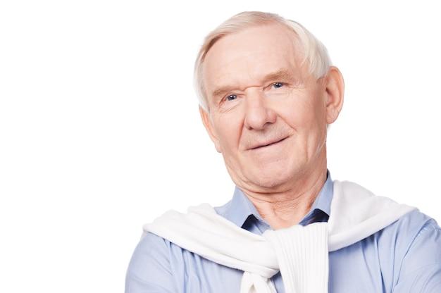 自信のある年配の男性。白い背景に立っている間カメラで笑っている年配の男性の肖像画