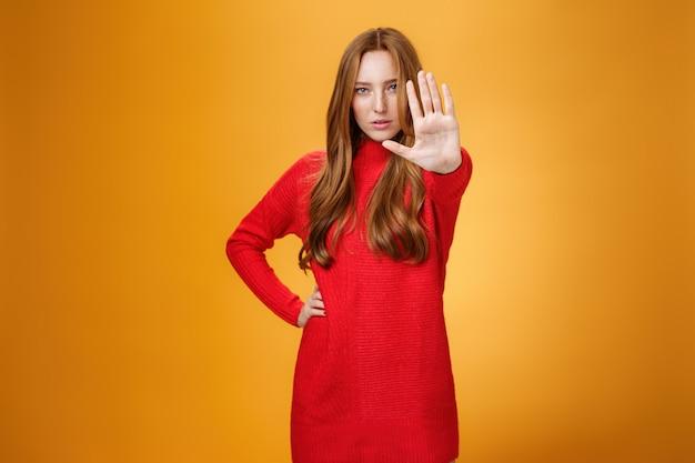 자신감 넘치는 관능적이고 매력적인 빨간 머리 여성은 정지 상태에서 카메라를 향해 손바닥을 내밀고 정지를 요구하는 금지 제스처와 주황색 배경 위에 서 있습니다.
