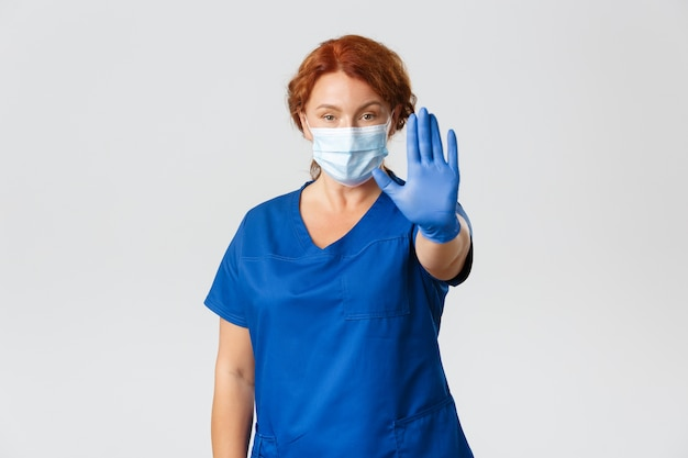 Confident and serious female doctor, physician disapprove or disagree, wear face mask and gloves, show stop, prohibition move.