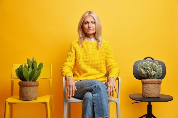 Confident serious female pensioner poses between two chairs with cactus